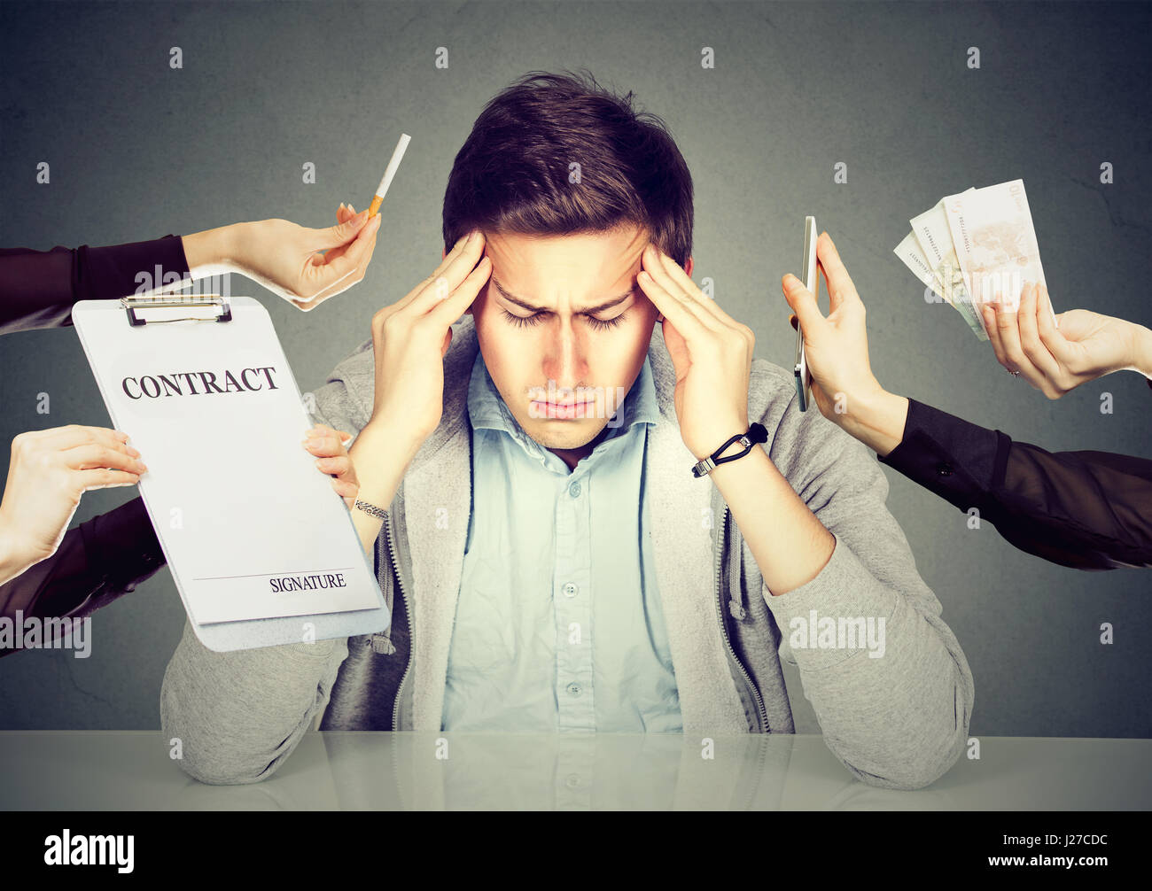 Desperate sad young man leaning on a desk. Stressed guy overwhelmed by things errands should be done. Human face - Stock Image