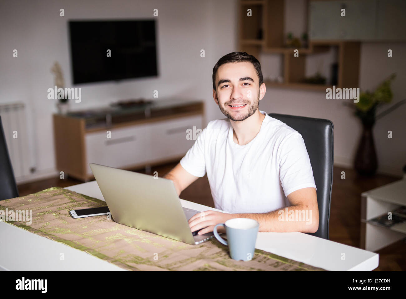 Pensive young man with coffee cup standing at table with laptop Stock Photo