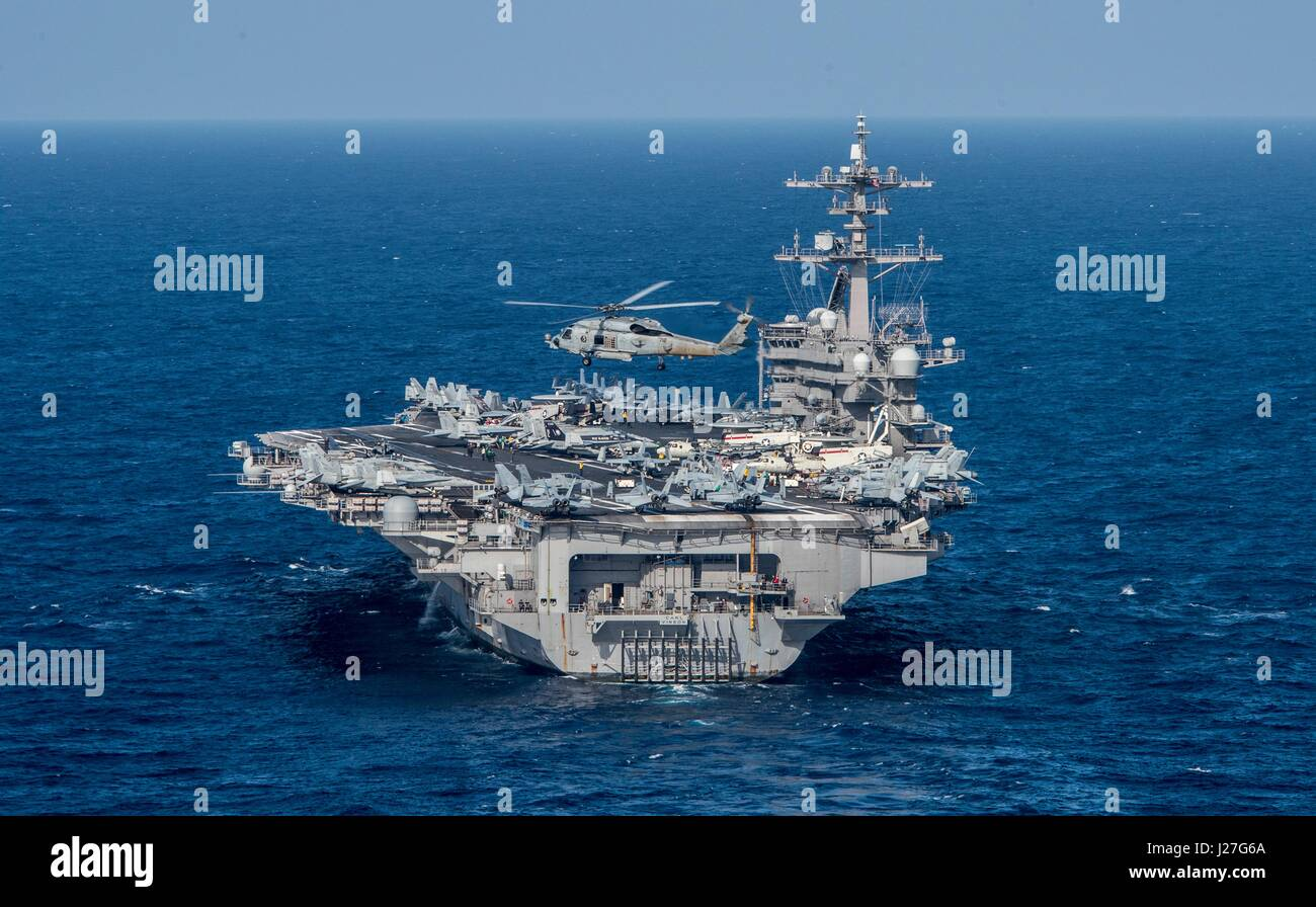 The U.S. Navy MH-60R Sea Hawk helicopter approaches the Nimitz-class aircraft carrier USS Carl Vinson as it transits - Stock Image