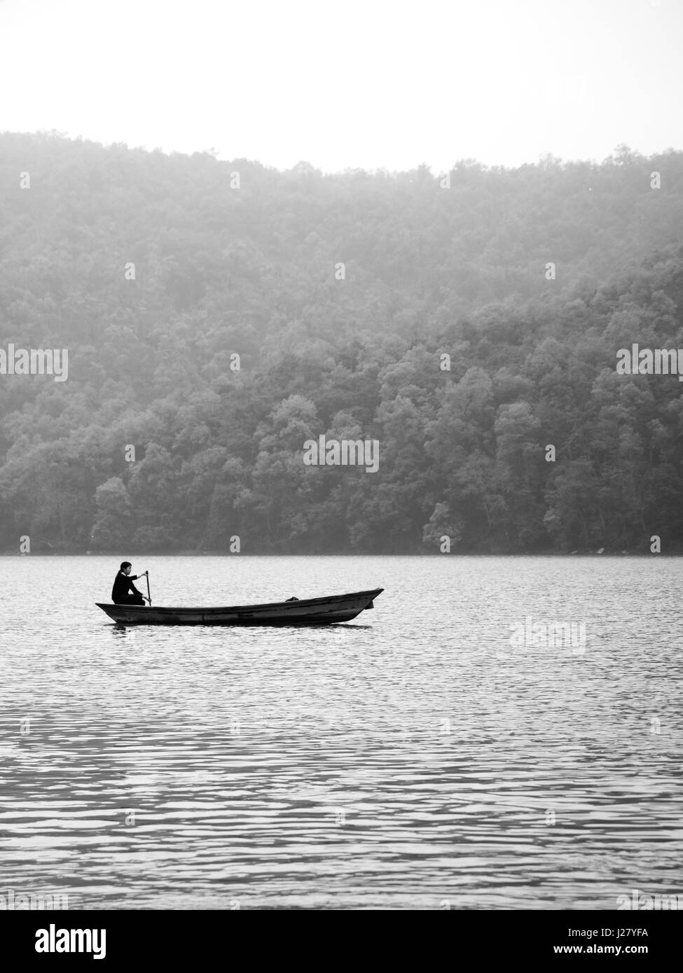 A woman alone in a canoe boat paddling on Fewa Lake, Pokhara on a misty morning in black and white. Pokhara, Nepal. - Stock Image
