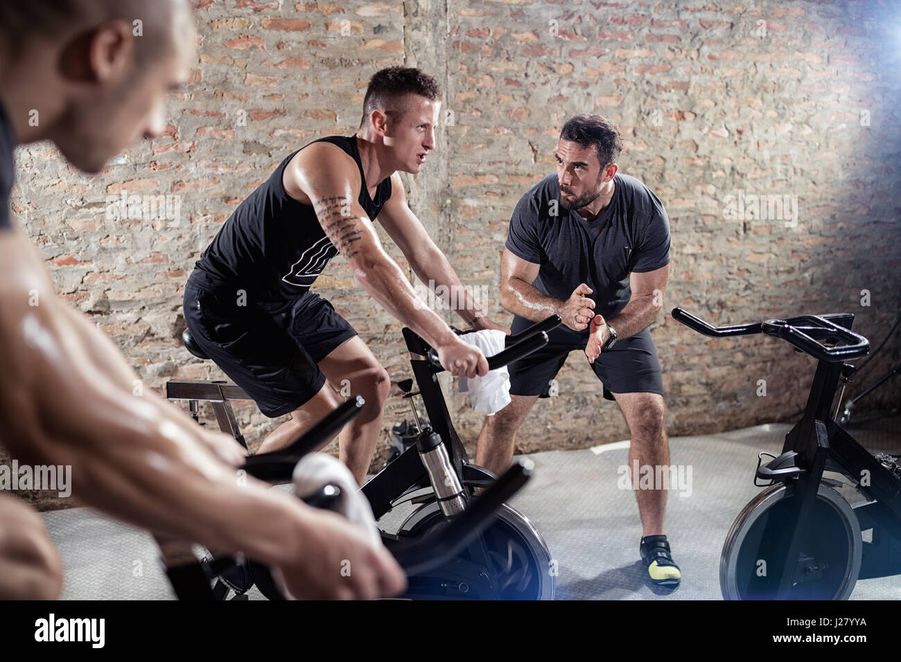 trainer gives support young man on a spinning training - Stock Image