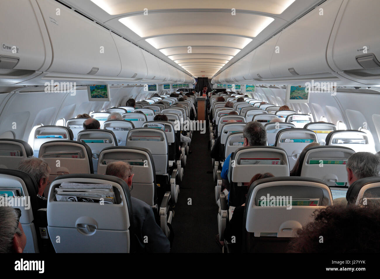 General view down plane cabin of a full passenger plane (in this case a BA Airbus A320-200). - Stock Image