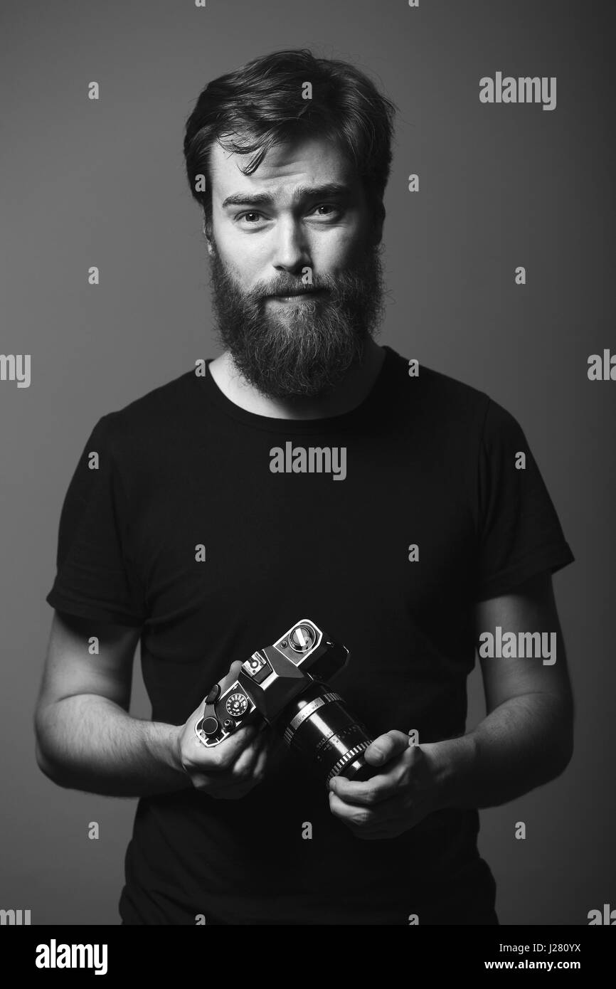 Portrait of a handsome photographer holding SLR camera. - Stock Image