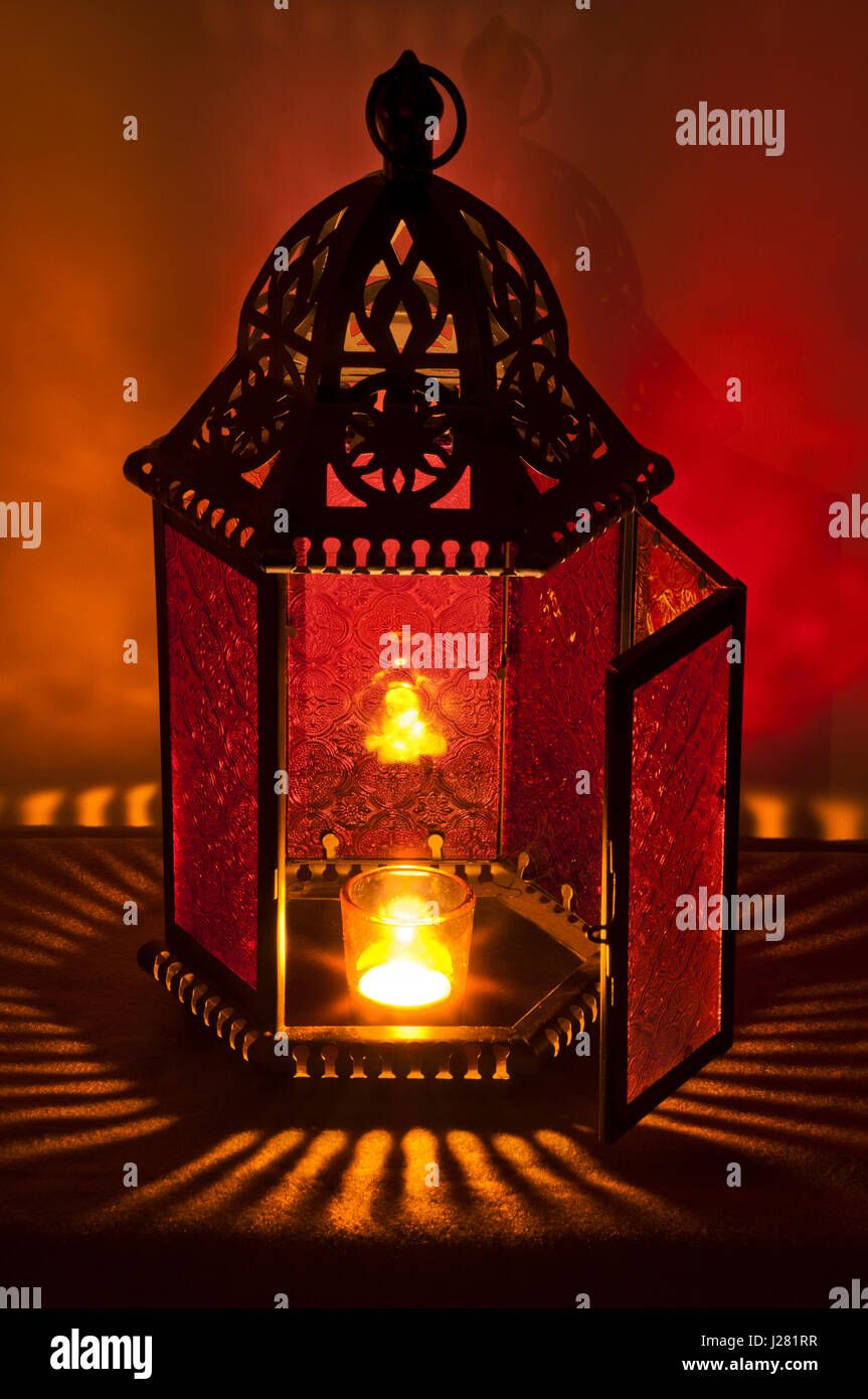 Metal Vintage Lantern Lit By Candlelight With Deep Red And Gold Colors