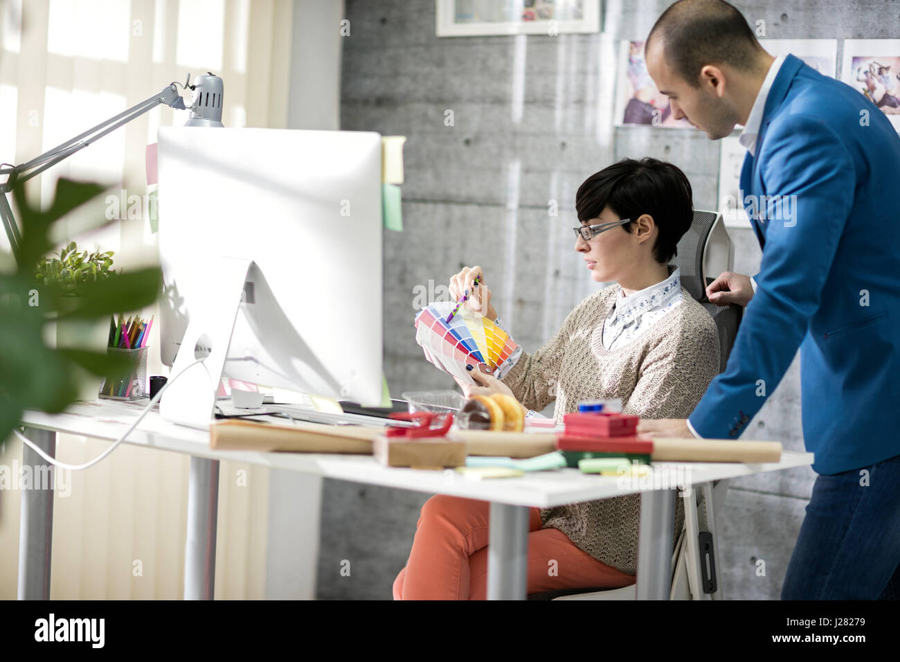 Female designer with male colleagues at design studio - Stock Image