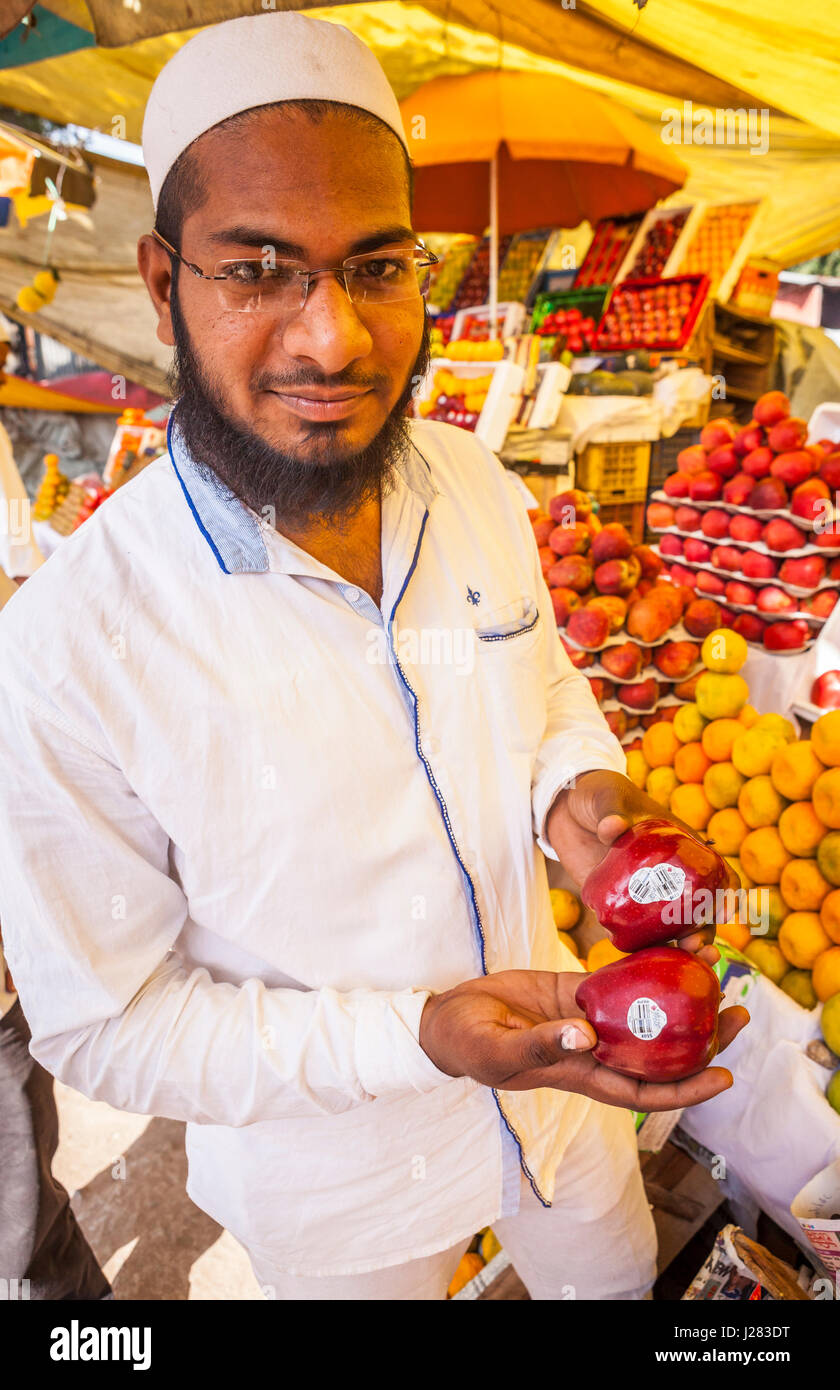 An Indian man in a fruit market in Pune, India holding up apples from Washington State, USA. - Stock Image