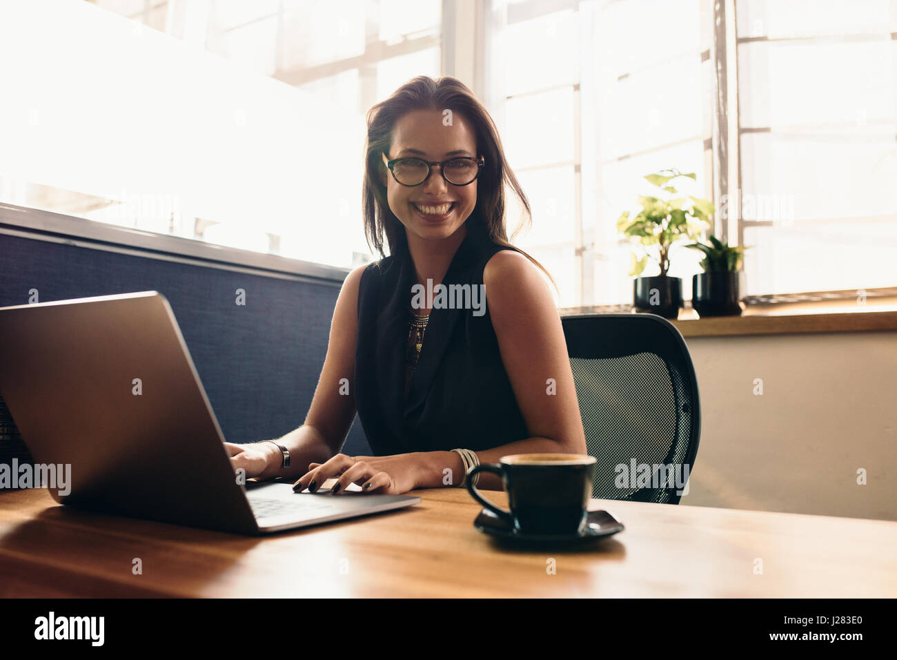 Female vlogger editing her vlog on Computer. Smiling young woman at her desk in office working on computer with - Stock Image