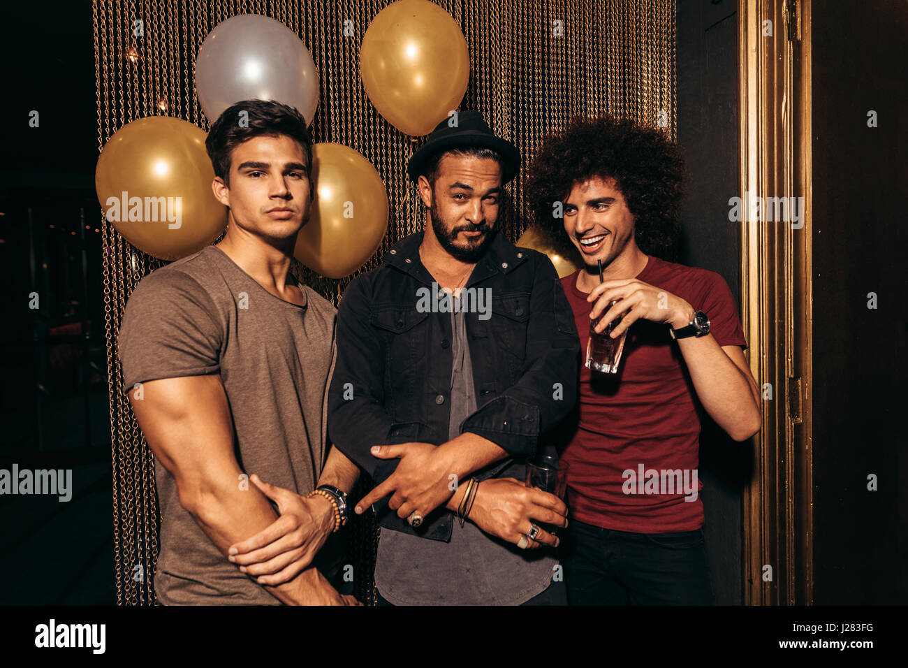 Portrait of three young men partying at the nightclub. Group of men having good times at pub. - Stock Image