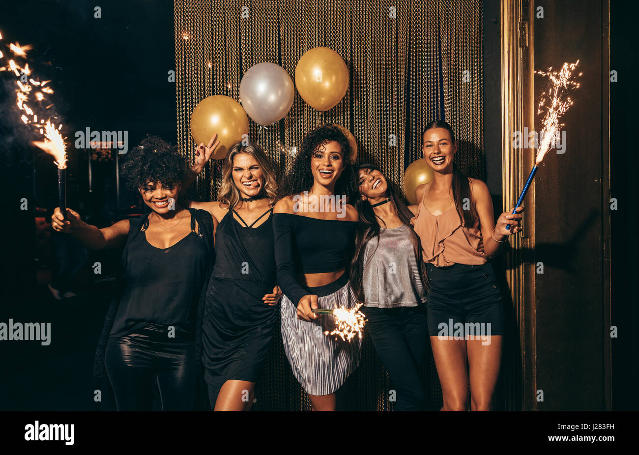Shot of group of girls celebrating new years eve at the nightclub. Group of female friends partying in pub with - Stock Image
