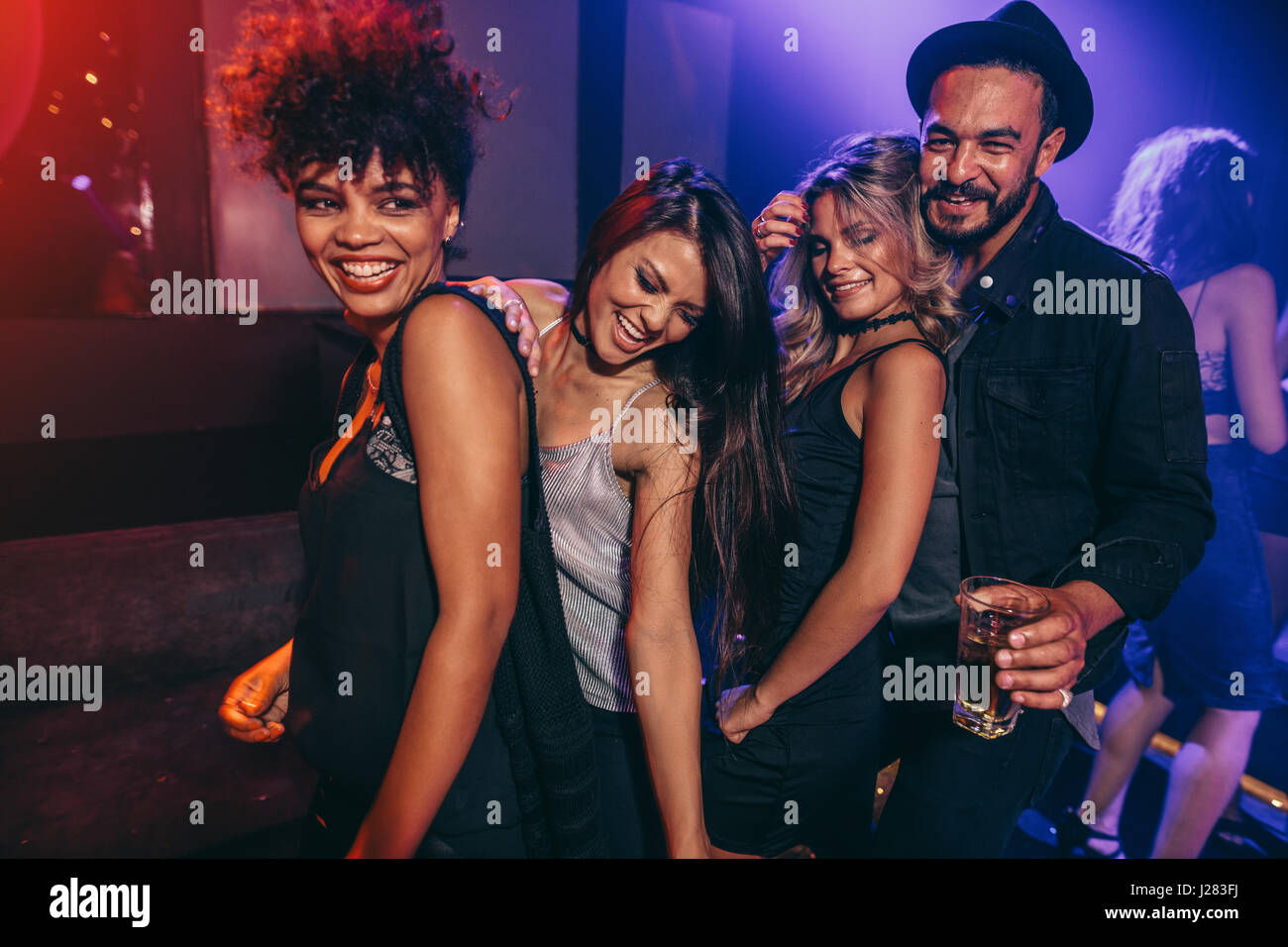 Young man and woman enjoying a party at nightclub. Group of friends dancing at disco club. - Stock Image