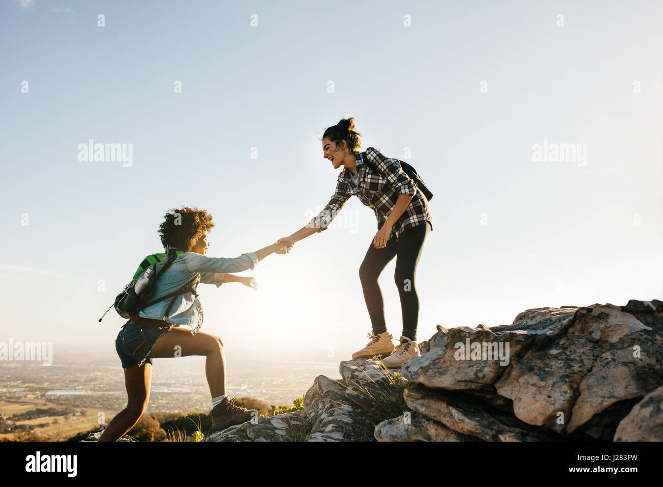Young woman helping friend to climb up the rock. Two young females hiking in nature. - Stock Image