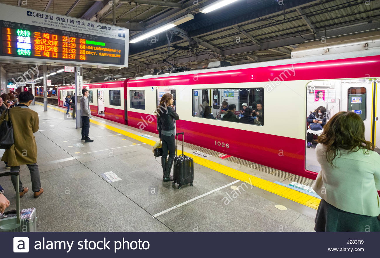 Electronic informational sign above passengers standing on train platform 1 in Ebisu Station, Shibuya, Tokyo, Honshu, - Stock Image