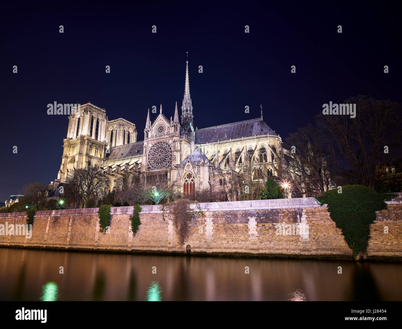 Low angle view of Notre Dame de Paris by Seine river against clear sky at night - Stock Image