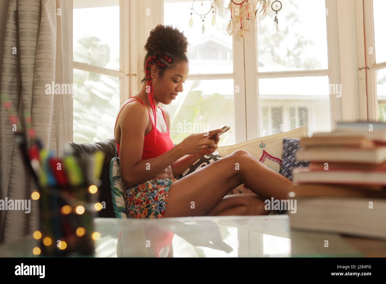 Black girl lying on couch and using smartphone, young african american woman relaxing with mobile phone. Happy latina - Stock Image