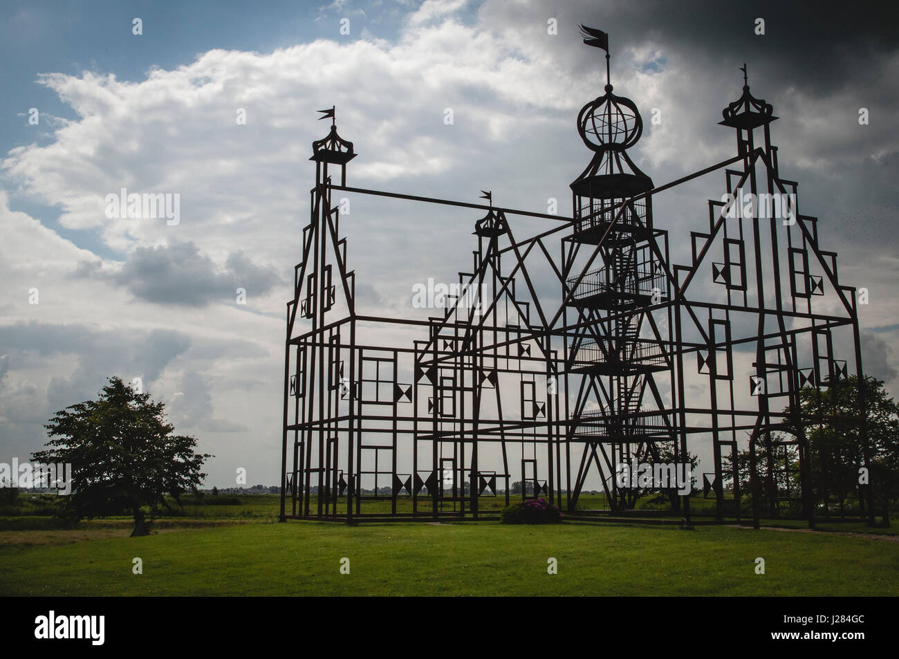 Silhouette built structure on grassy field against cloudy sky - Stock Image