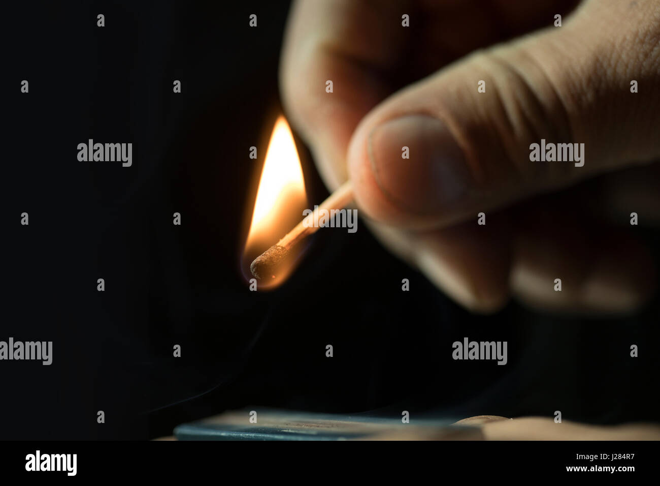 Cropped hand holding burning matchstick in darkroom - Stock Image