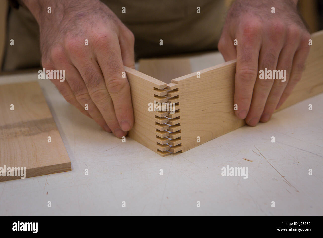 Midsection of carpenter joining wooden planks at table in workshop - Stock Image