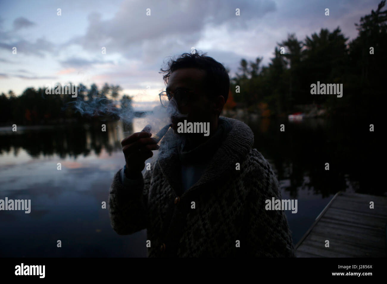 Man smoking with vape while standing on jetty against cloudy sky during sunset - Stock Image
