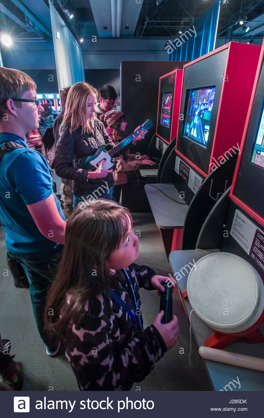 "Children and adults playing interactive musical videogames at a Special Exhibition: ""GAME ON: Why are videogames - Stock Image"