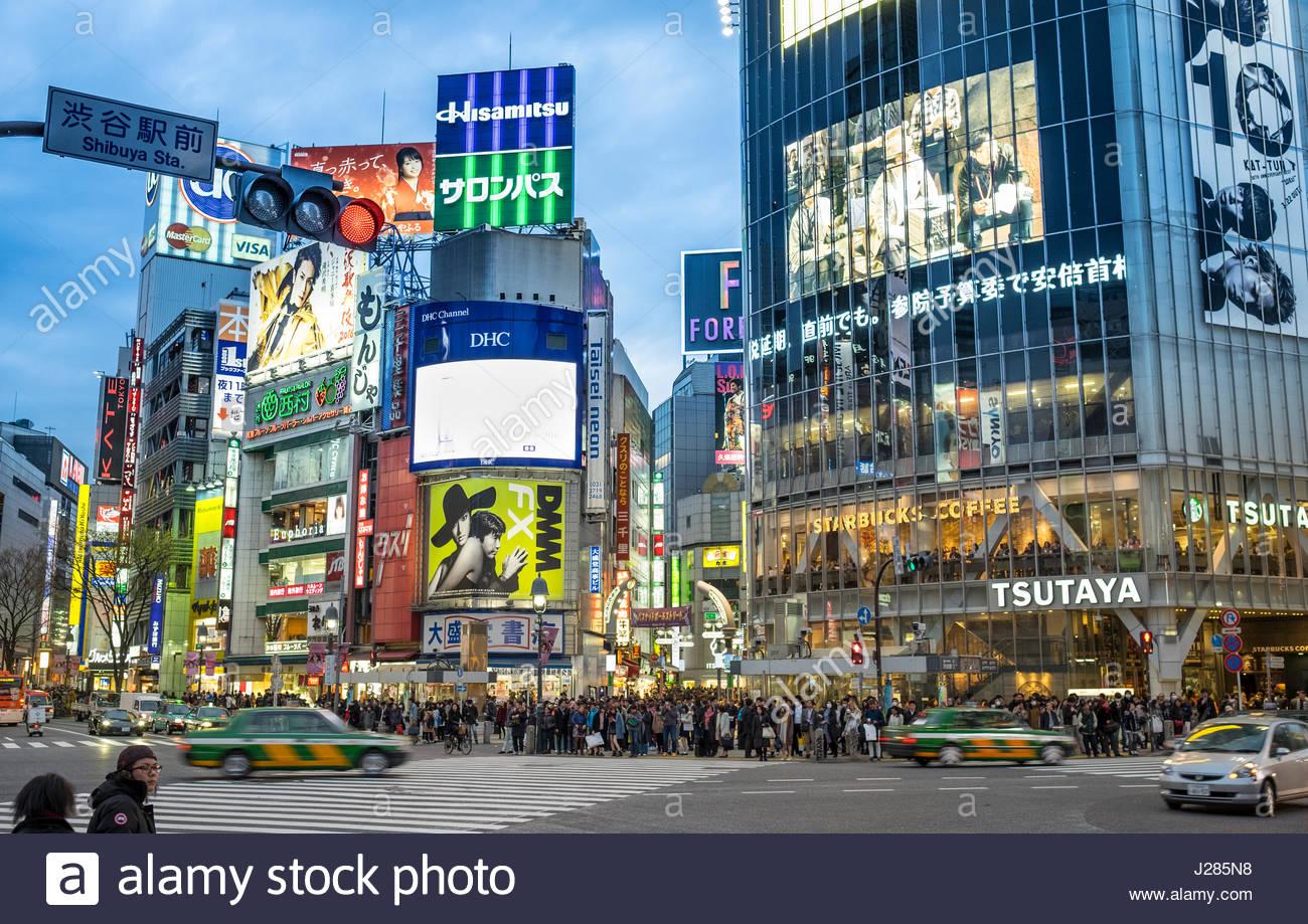 The world famous pedestrian scramble in front of Shibuya Station at dusk, Shibuya, Tokyo, Honshu, Japan - Stock Image