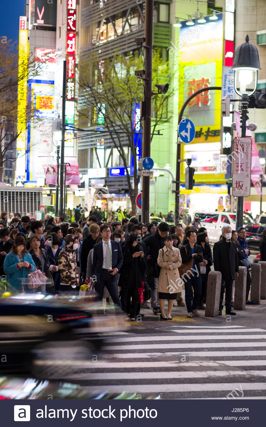 People waiting to cross the world famous pedestrian scramble in front of Shibuya Station at dusk, Shibuya, Tokyo, - Stock Image