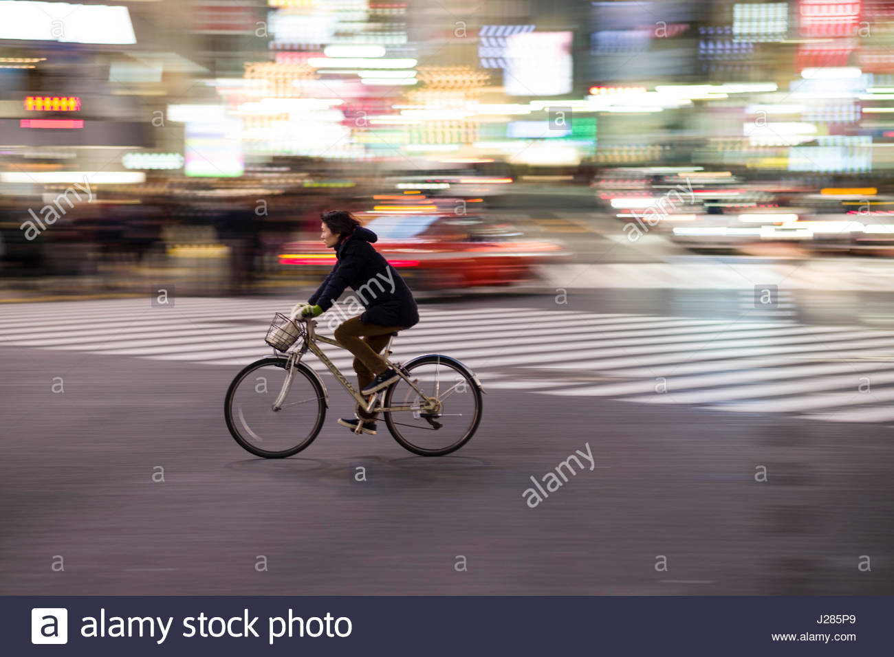 Panning image of bicyclist crossing the famous pedestrian scramble in front of Shibuya Station at dusk, Shibuya, - Stock Image