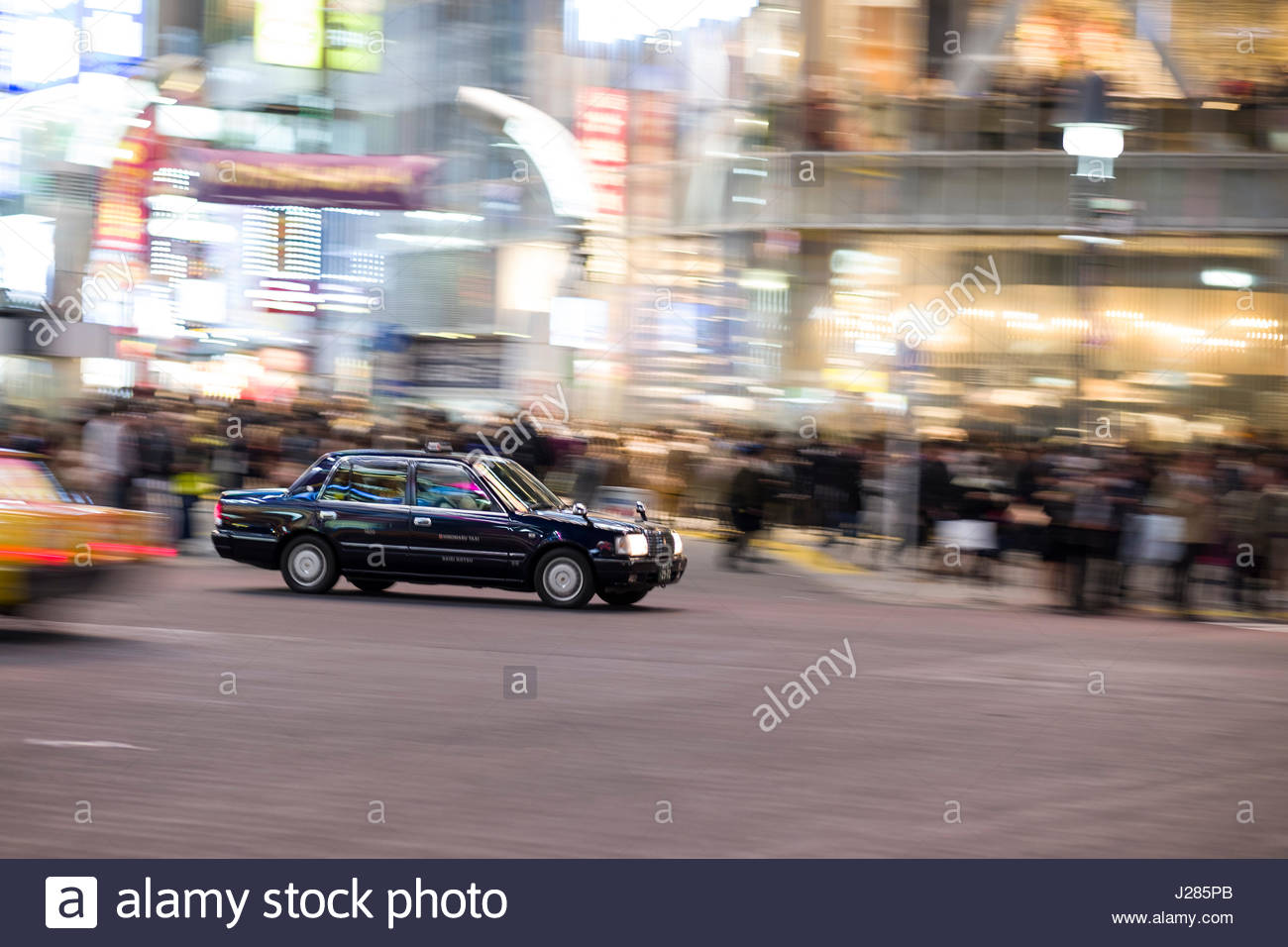 Panning image of taxi crossing the famous pedestrian scramble in front of Shibuya Station at dusk, Shibuya, Tokyo, - Stock Image