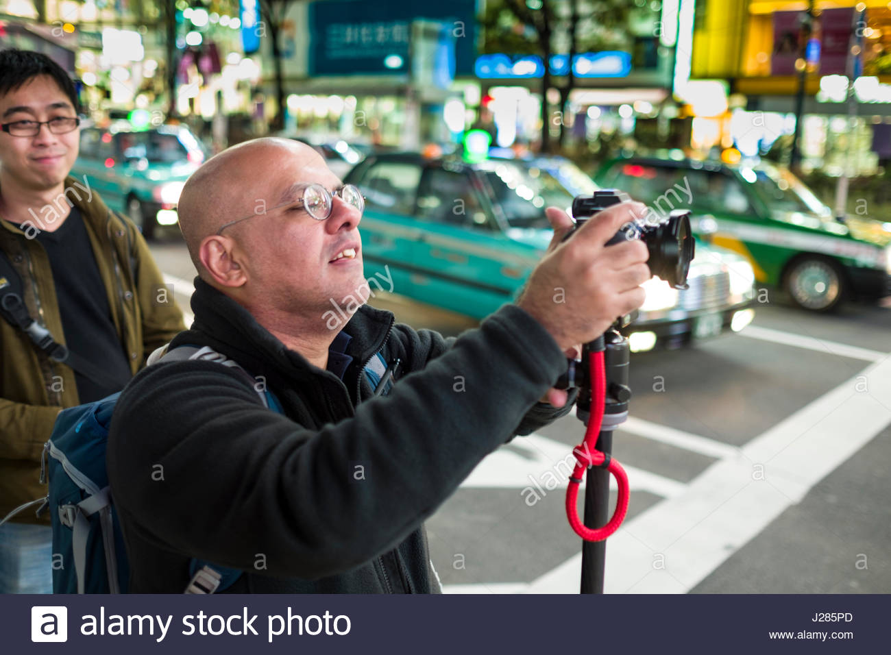Male photographer photographing the world famous pedestrian scramble in front of Shibuya Station at dusk, Shibuya, - Stock Image