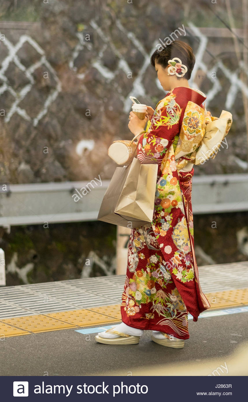 Japanese woman dressed in colorful traditional kimono standing on train platform holding a paper cup and using an - Stock Image