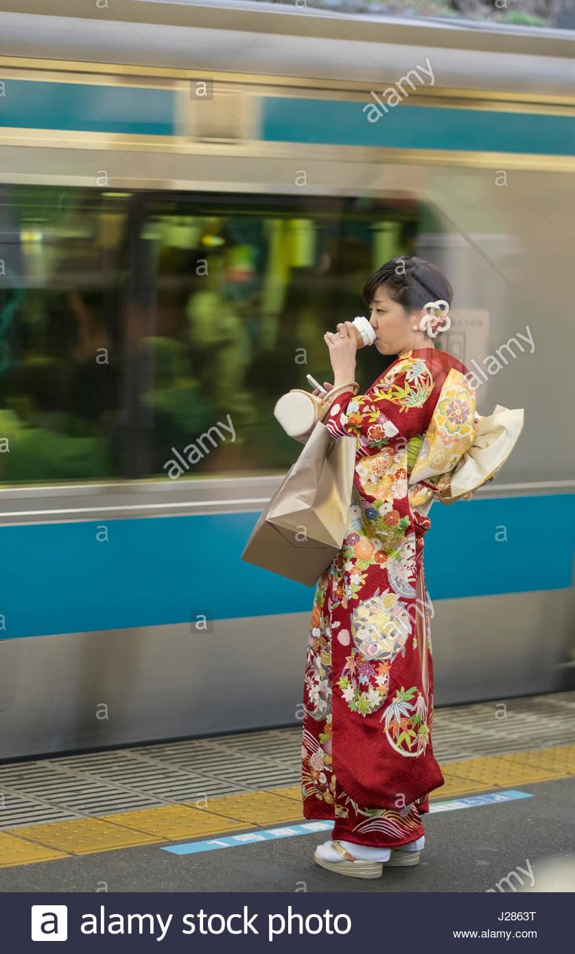 Japanese woman dressed in colorful traditional kimono standing on train platform drinking from a paper cup and using - Stock Image