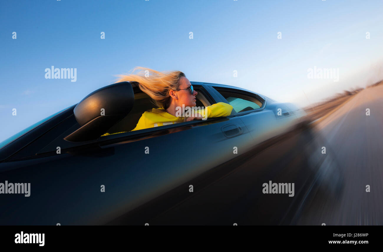 Young woman speeding down the road an looking out the window - Stock Image