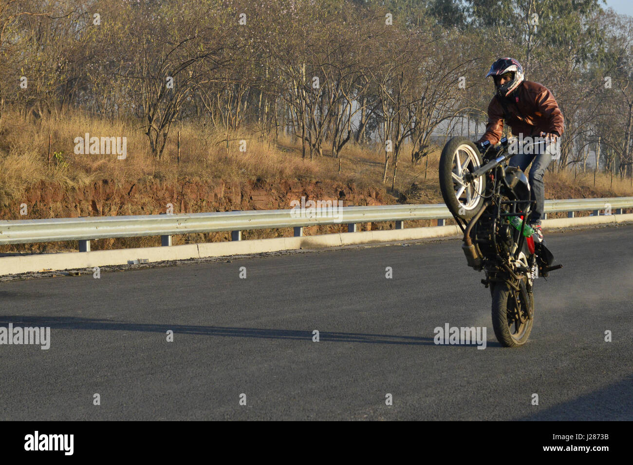 Stunt motorcycle rider performing at a local road near Pune, Maharashtra - Stock Image