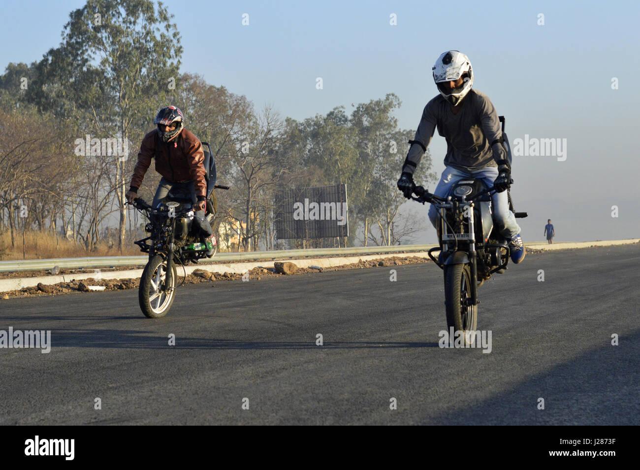 Two stunt motorcycle riders making stoppie near Pune, Maharashtra - Stock Image