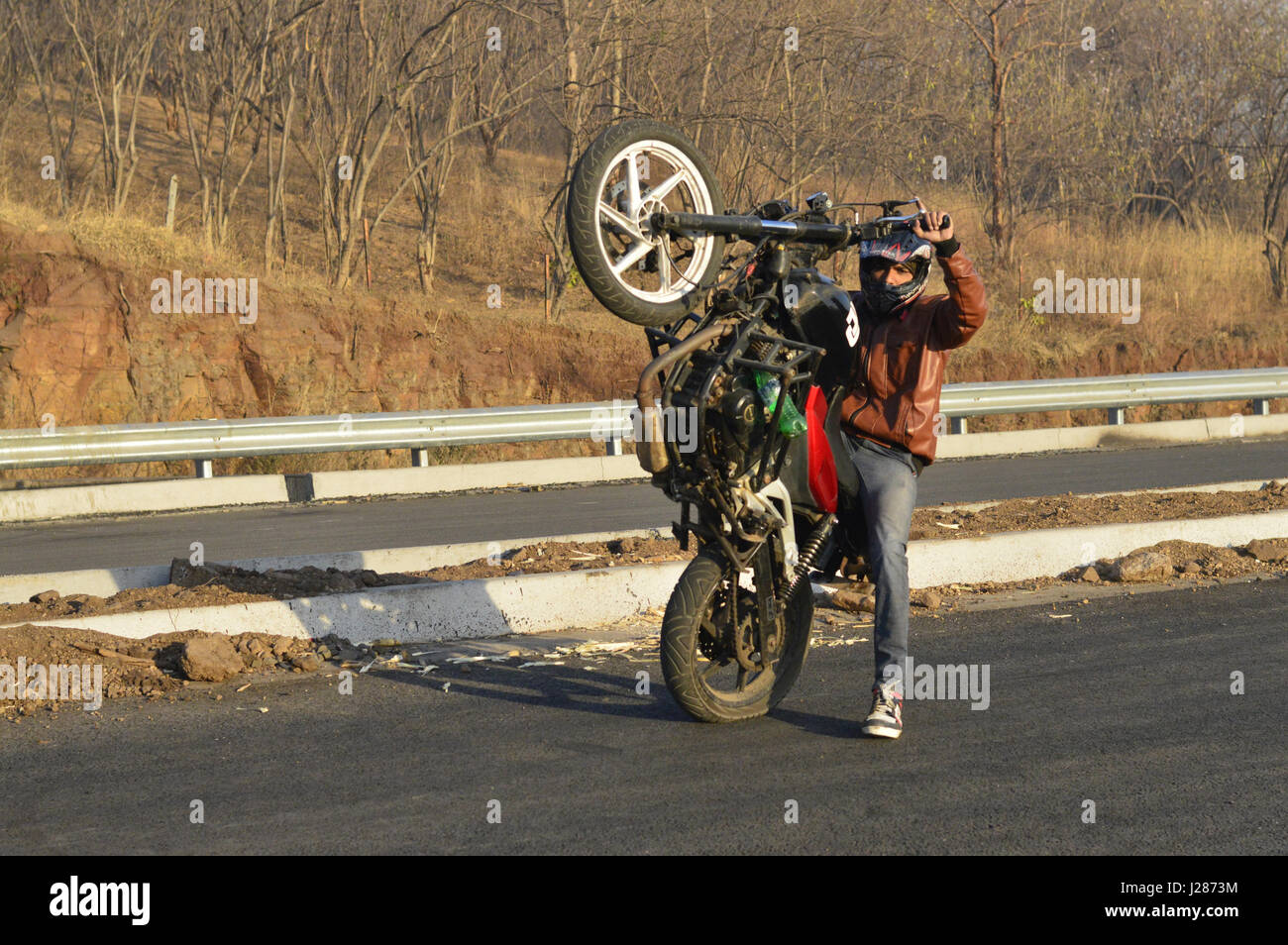 Stunt motorcycle rider performing at a local road near Pune, Maharashtra Stock Photo