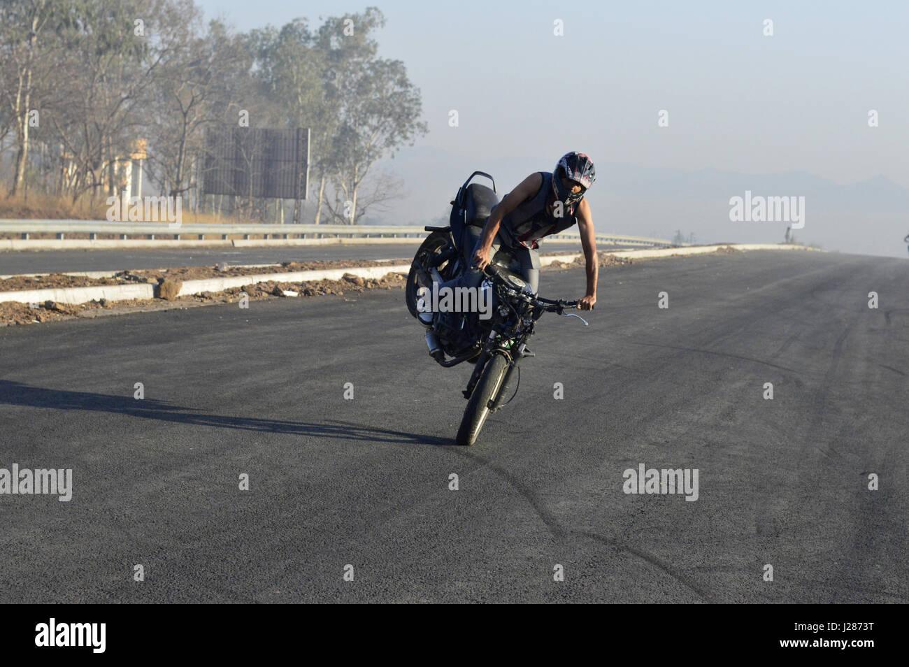 Stunt motorcycle rider making stoppie on a local road near Pune, Maharashtra - Stock Image