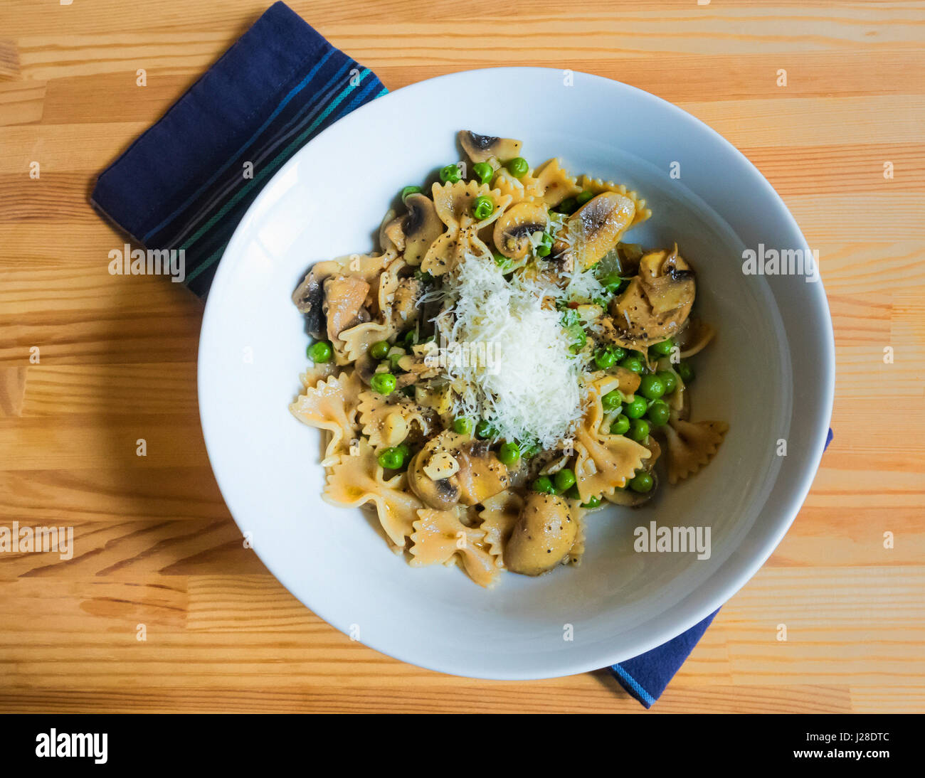 Bow tie pasta, with mushrooms, green peas and cheese in a white bowl - Stock Image