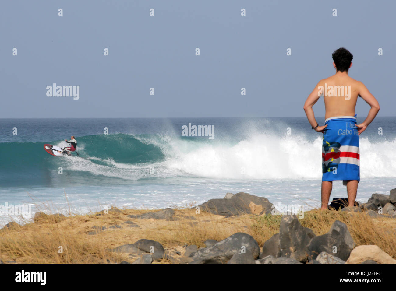 Man in a towel watching a surfer - Stock Image