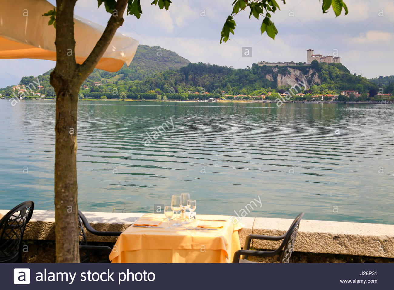 Italian restaurant table in Arona overlooking lake Maggiore and the castle of Angera - Stock Image