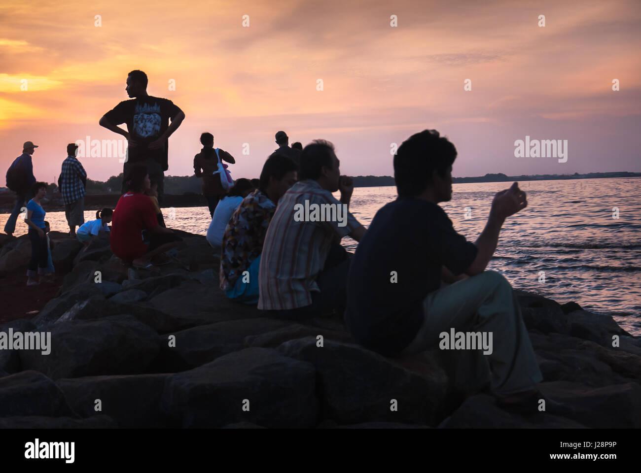 People having leisure time before sunset on the beach of Pantai Indah Kapuk, North Jakarta, Indonesia. © Reynold - Stock Image