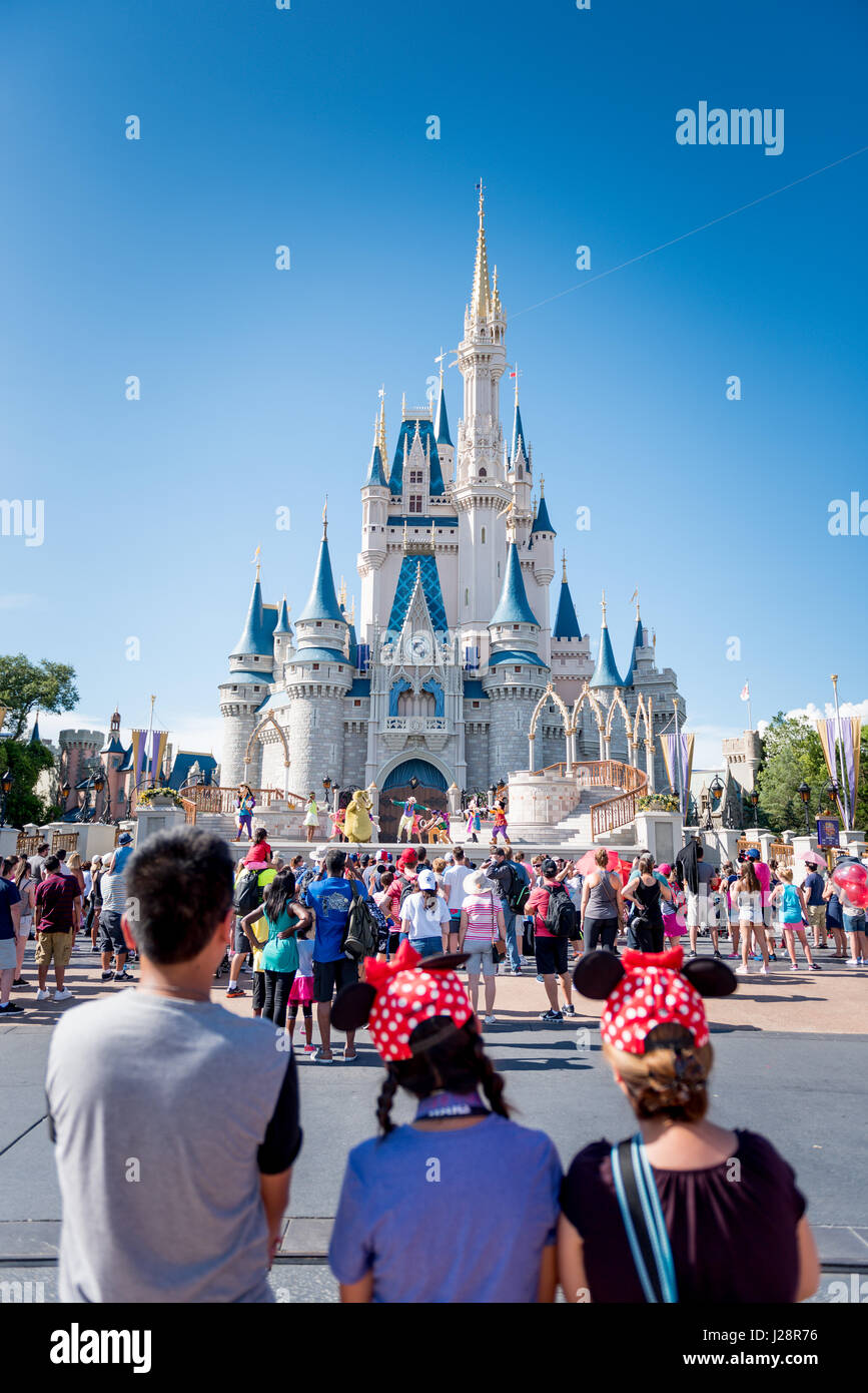 Mom, son and daughter watching performance of Mickey and Friends in front of Magic Kingdom Castle. - Stock Image