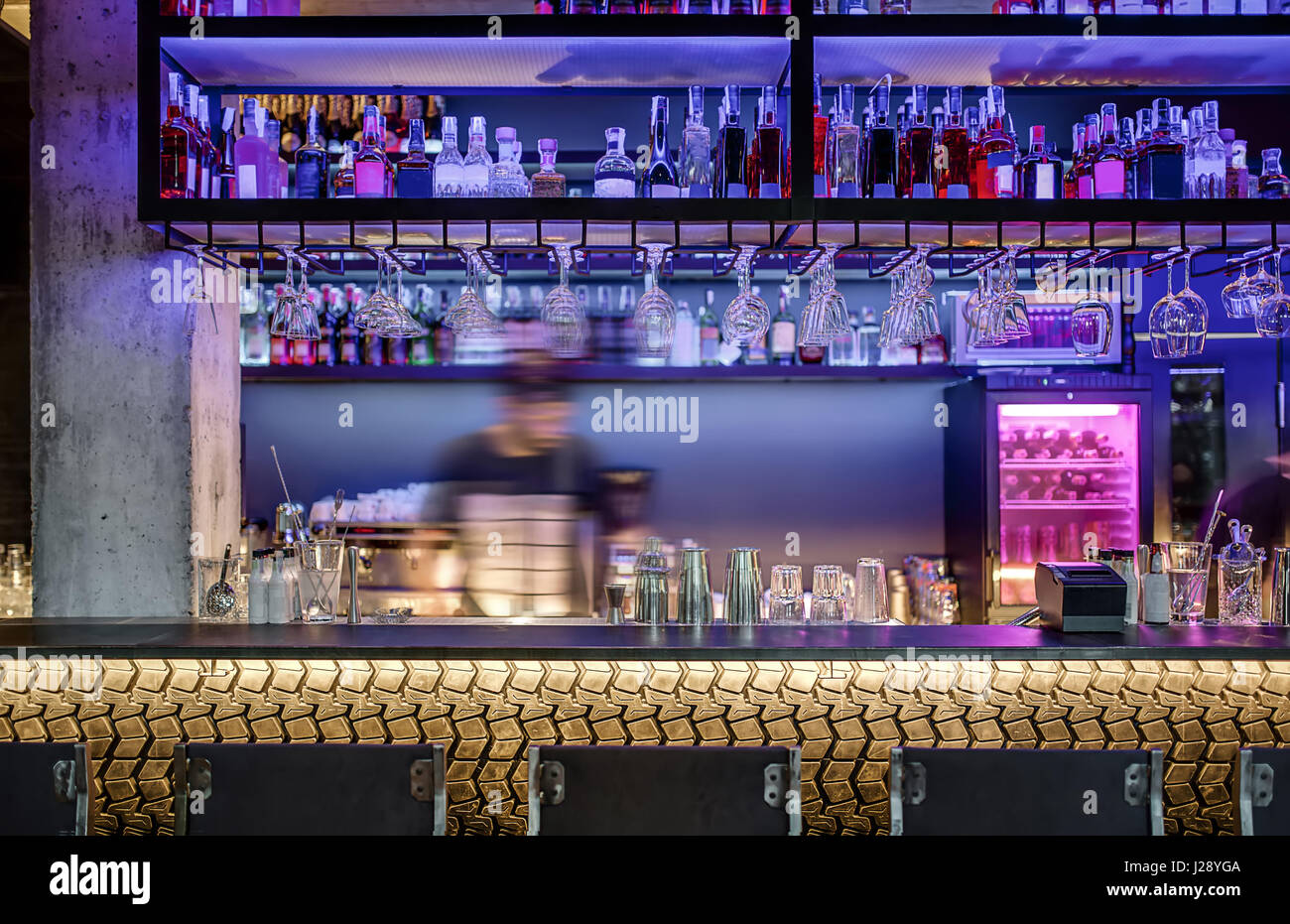 Luminous bar with a concrete column and a rack with the gold