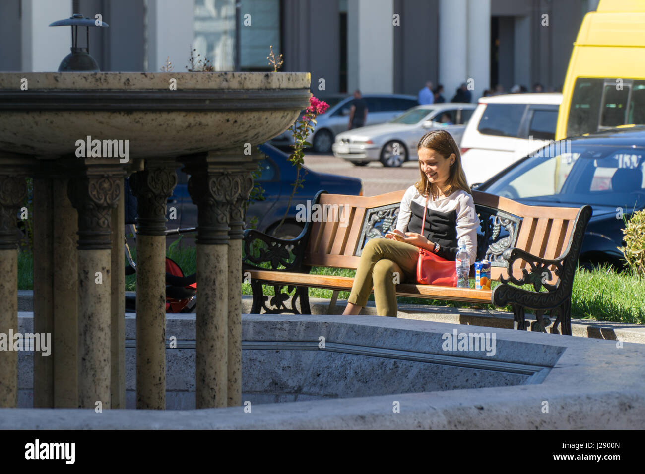 TBILISI, GEORGIA-SEP 25, 2016: Girl with telephone sitting on a bench in Liberty square. Stock Photo