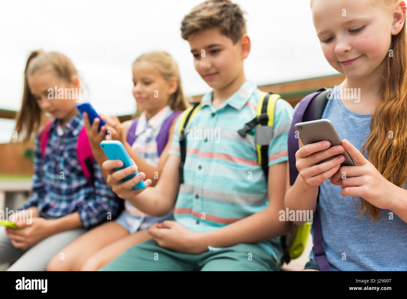 elementary school students with smartphones - Stock Image