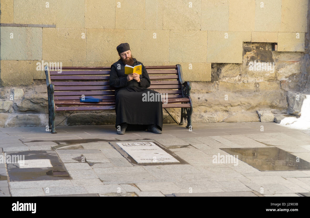 TBILISI, GEORGIA-SEP 25, 2016: Georgian priest reading a book sitting on a bench Stock Photo