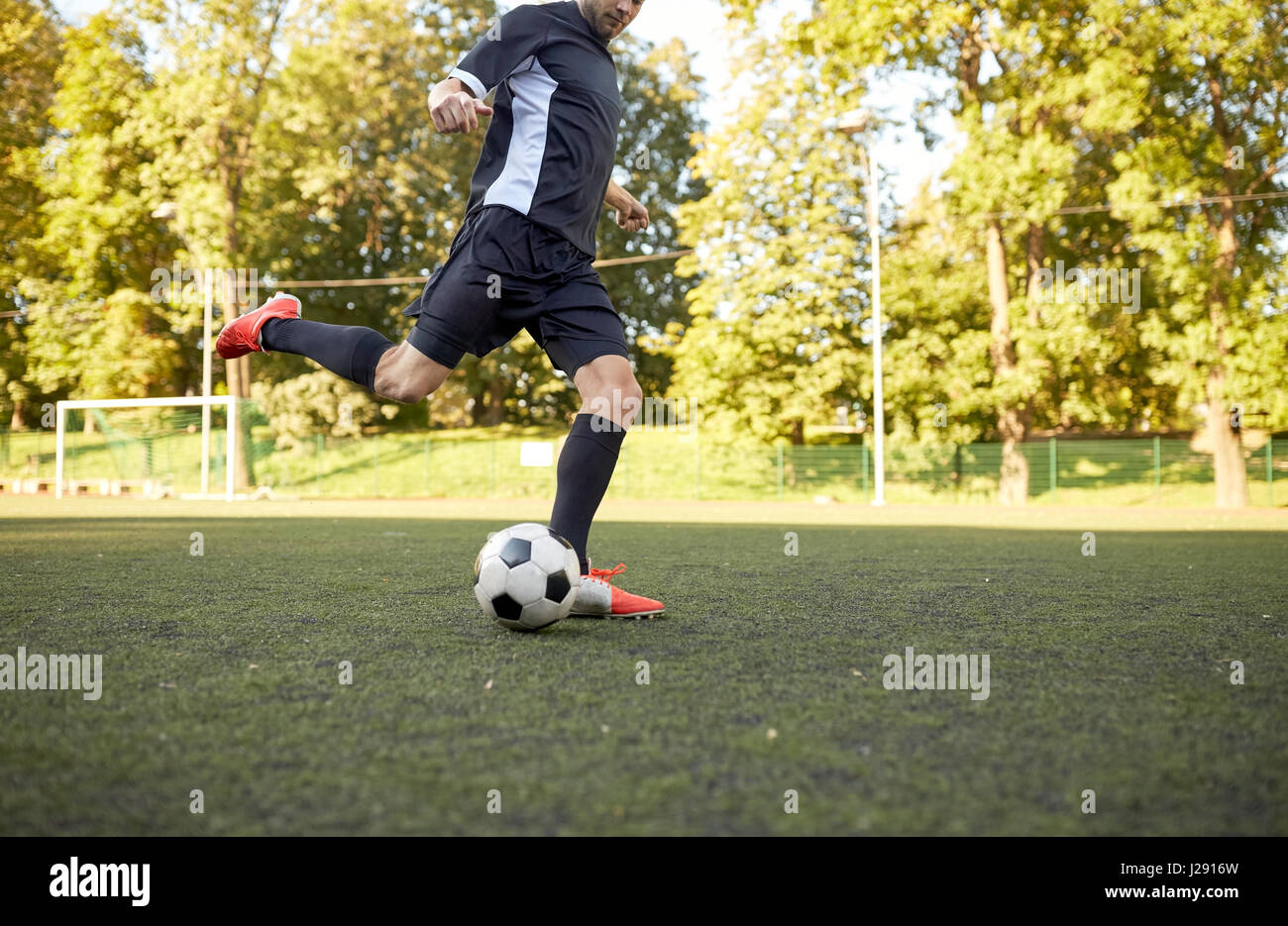 soccer player playing with ball on football field - Stock Image