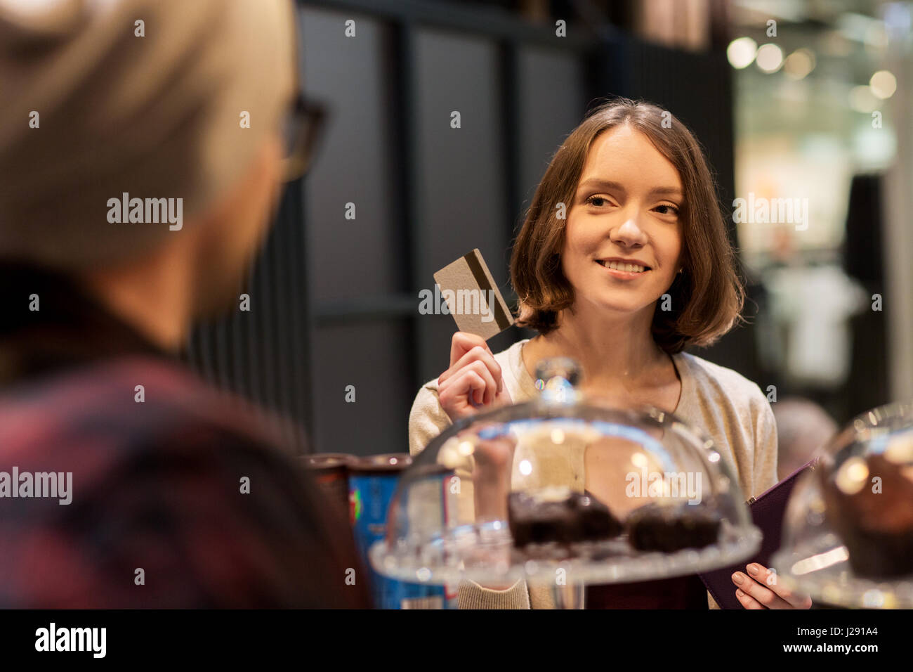 happy woman with credit card buying cakes at cafe - Stock Image