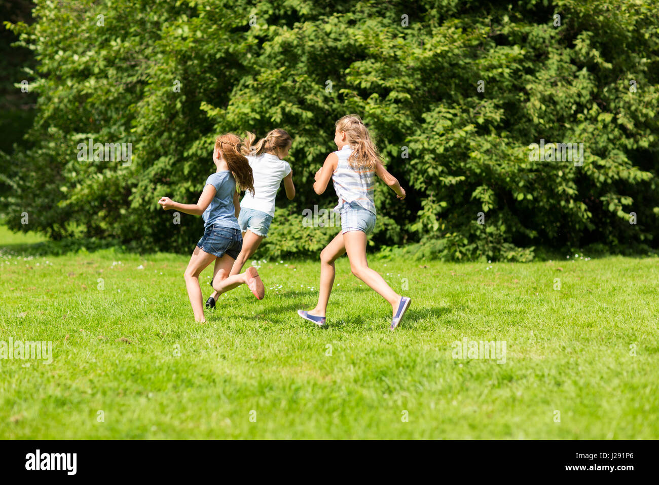 group of happy kids or friends playing outdoors - Stock Image
