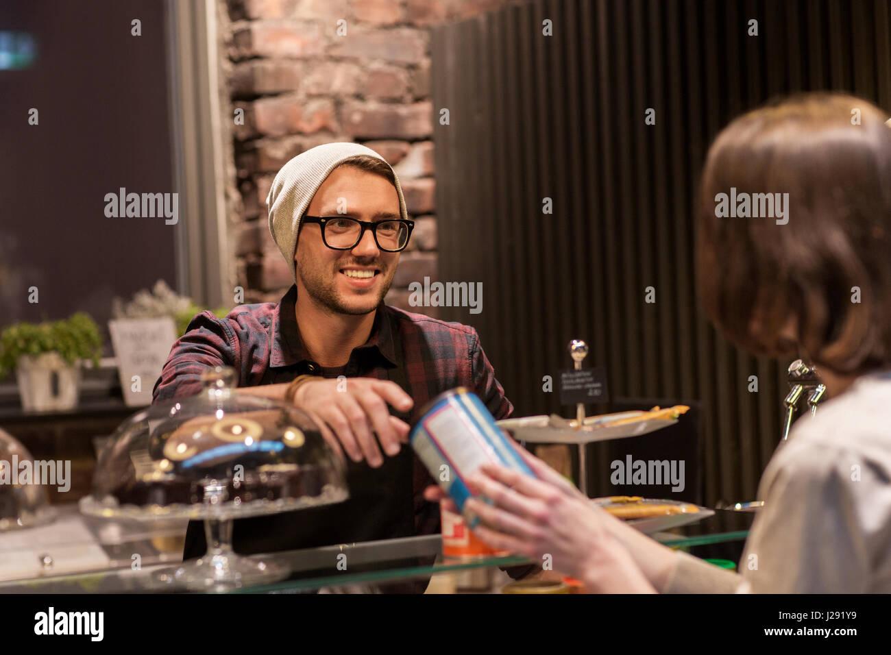 man or barman serving customer at vegan cafe - Stock Image