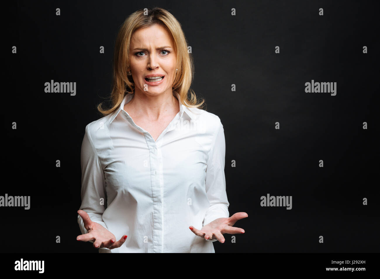 Discontented woman expressing dissatisfaction in the black colored studio - Stock Image