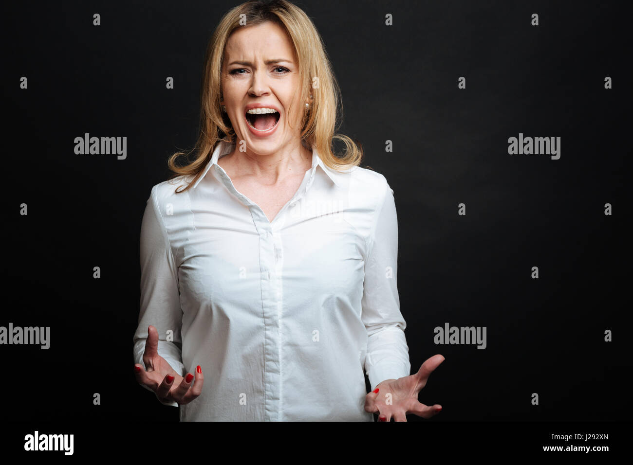 Irritated mature woman shouting in the studio - Stock Image